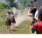 robbers shooting from horses by the train